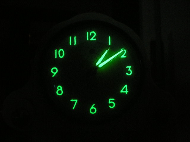 A glowing green watch dial floating in blackness.